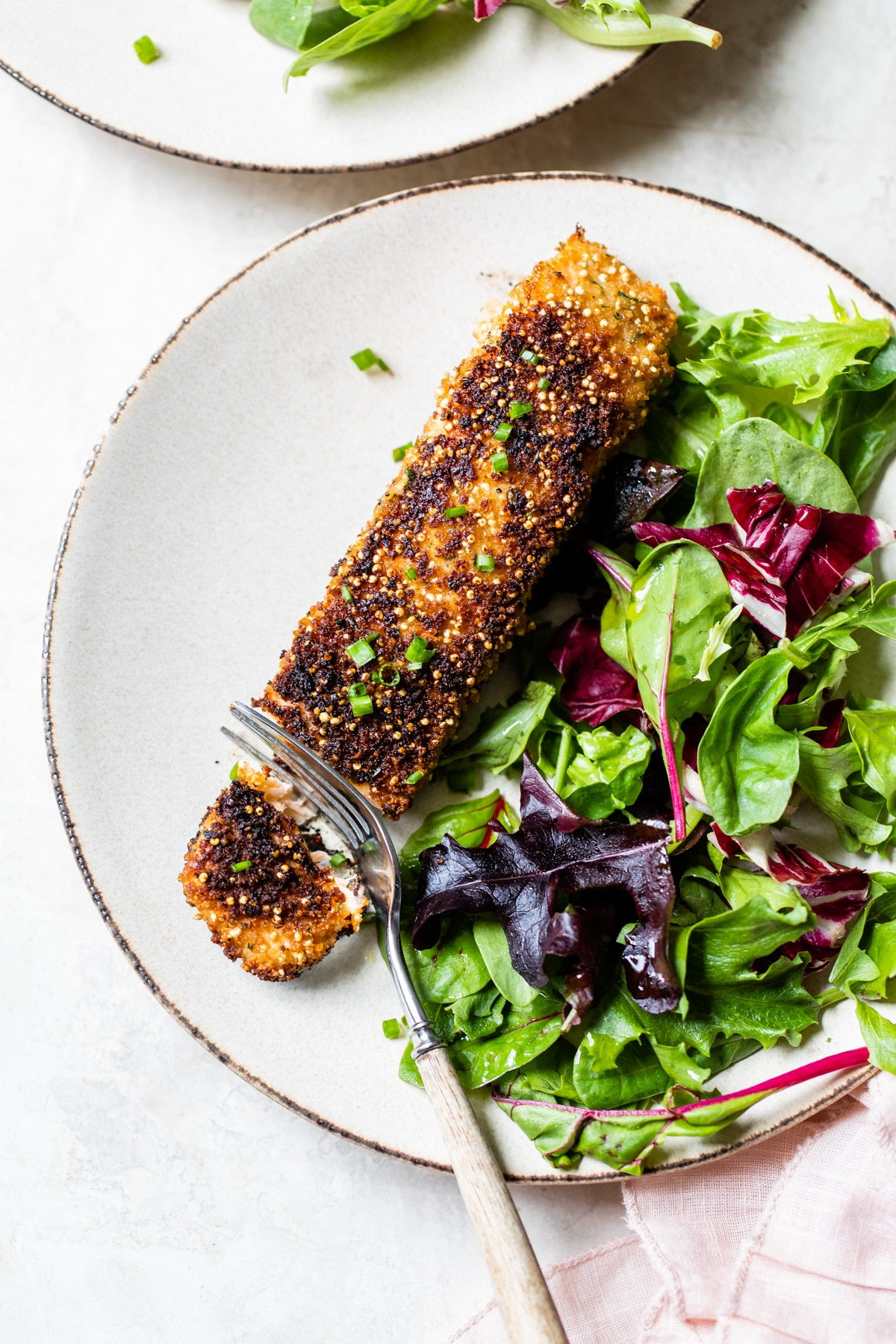 A plate of food on a table, with Salmon and Quinoa