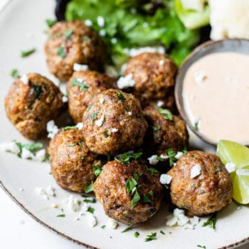 meatballs on a plate with side salad and sauce
