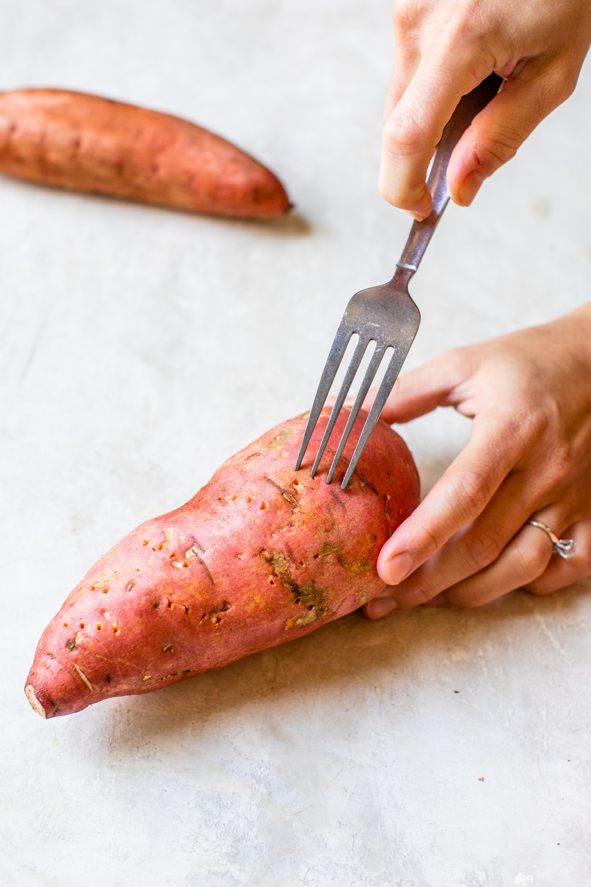 someone poking holes in a sweet potato
