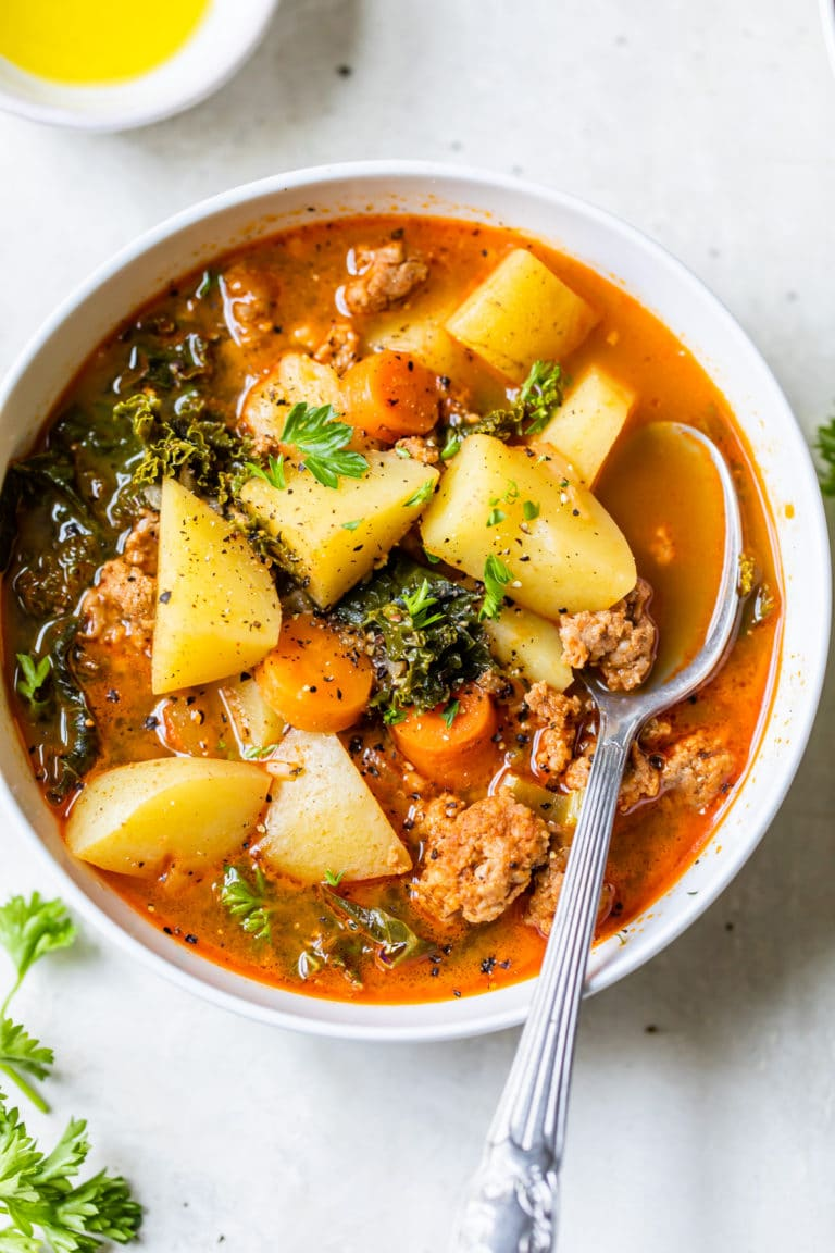 a bowl of soup with sausage and potatoes
