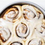 cinnamon rolls in a cake pan with text overlay