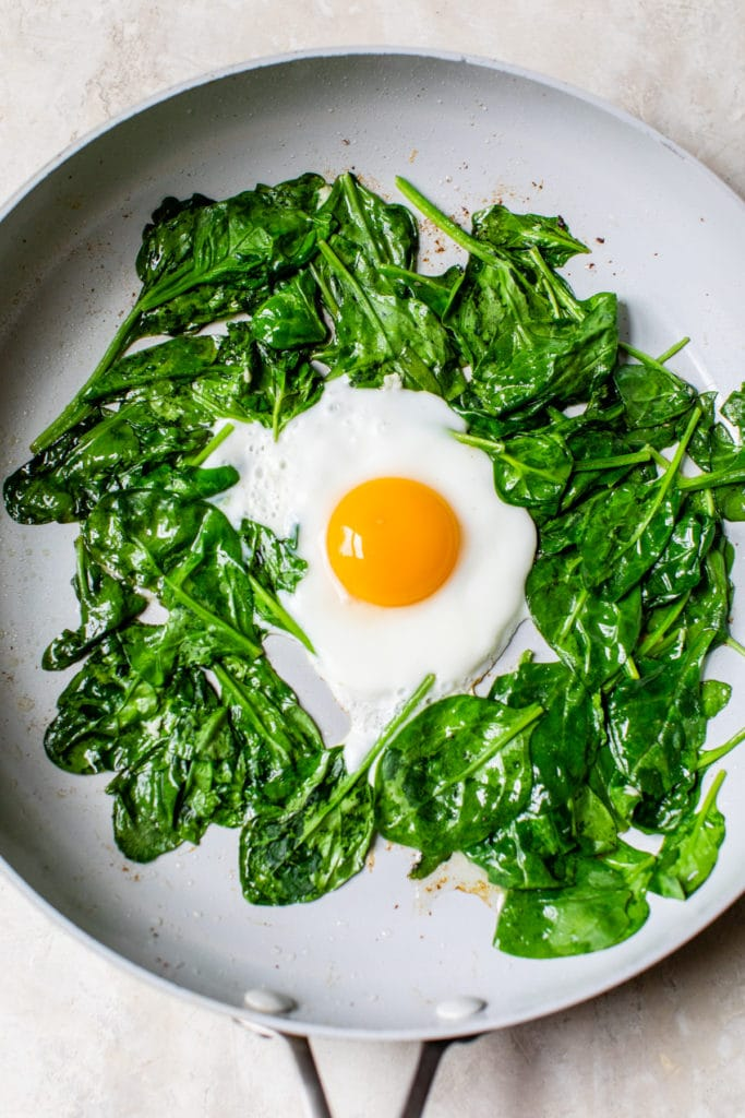 spinach and an egg in a skillet