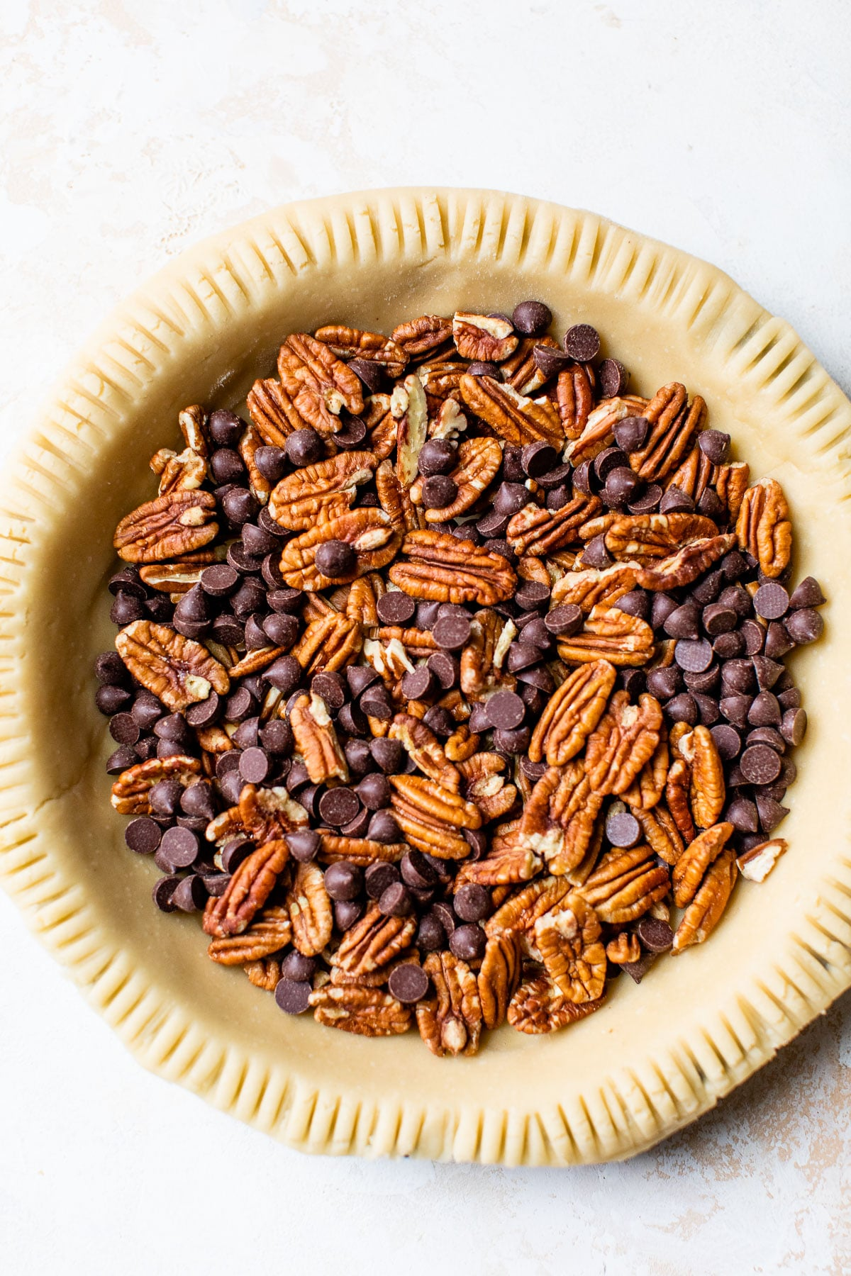 pie crust filled with pecans and chocolate chips