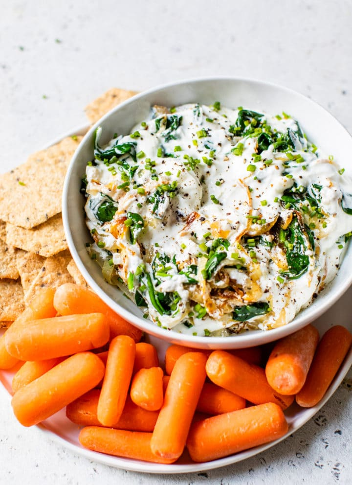 bowl with yogurt surrounded by baby carrots and crackers