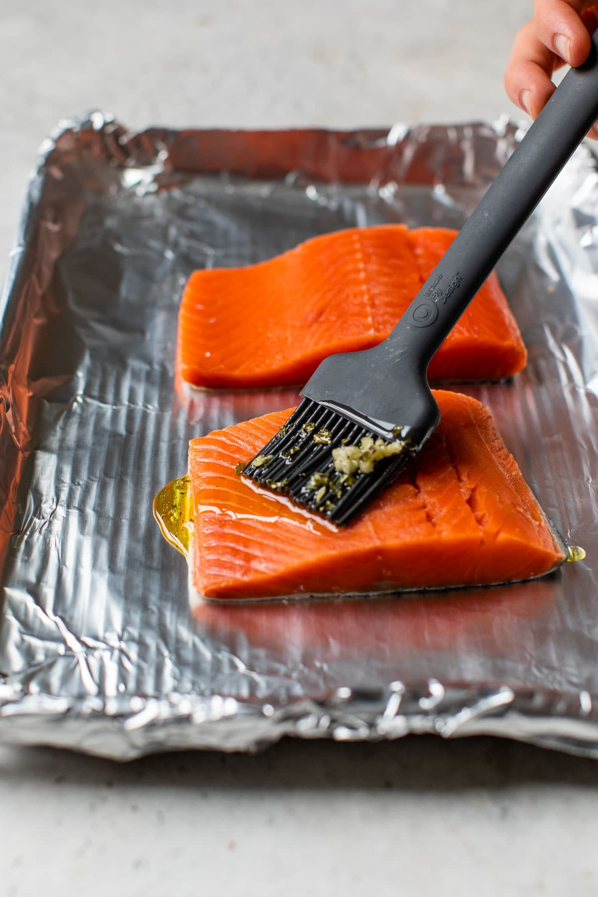 salmon fillet being brushed with olive oil