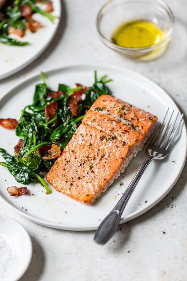 cooked salmon fillet on a plate with spinach