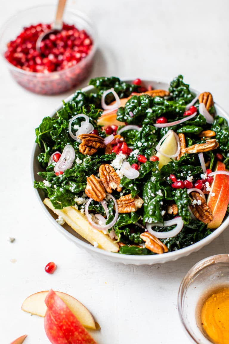 kale in a bowl with apple, pecans and pomegranate seeds