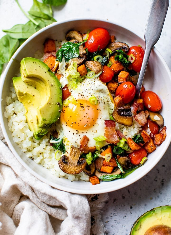 bowl filled with cauliflower rice, vegetables, avocado, and a fried egg