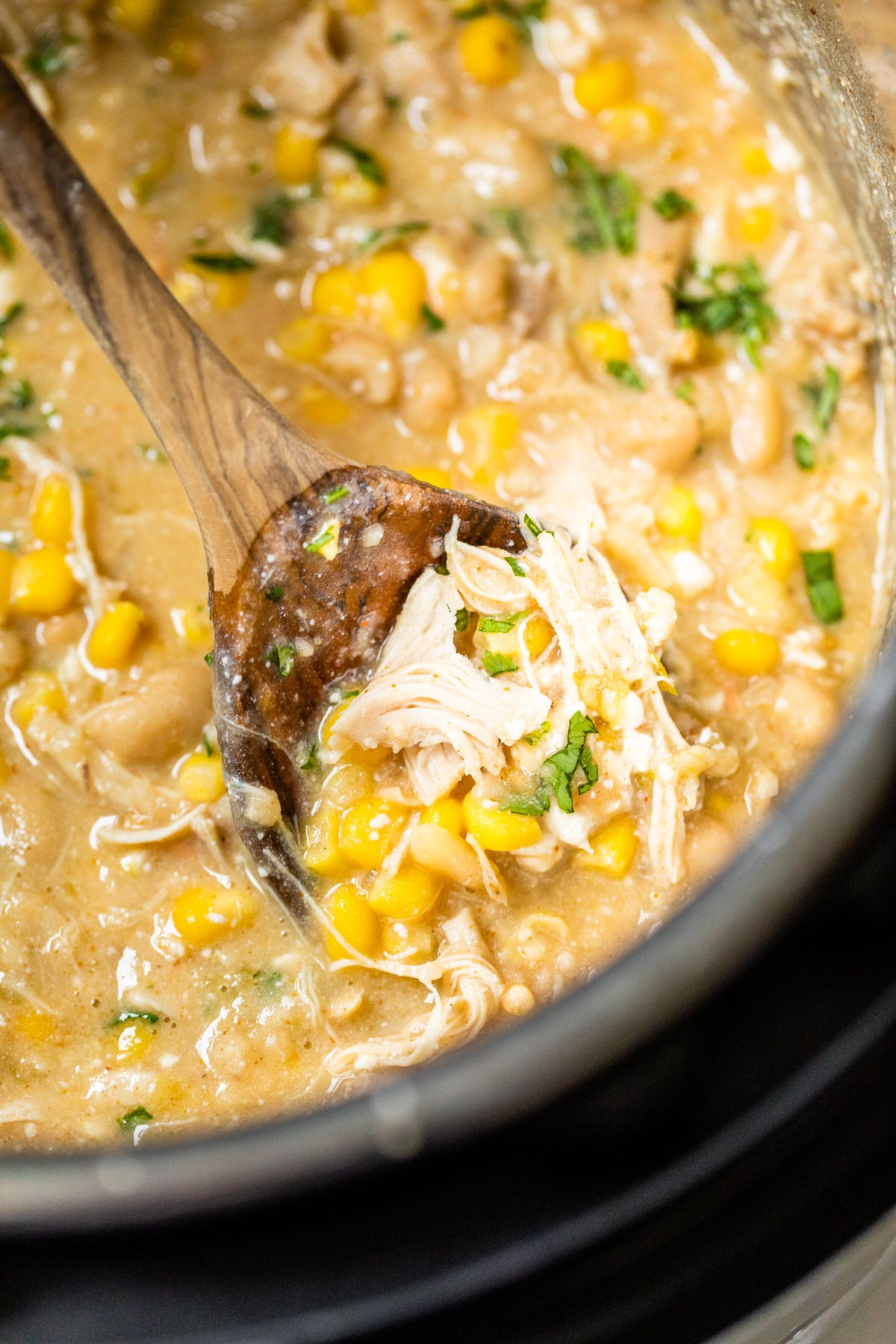 cooked shredded chicken, corn and broth in a pressure cooker