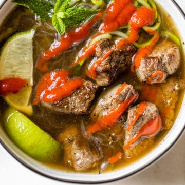 bowl of soup with beef topped with sriracha