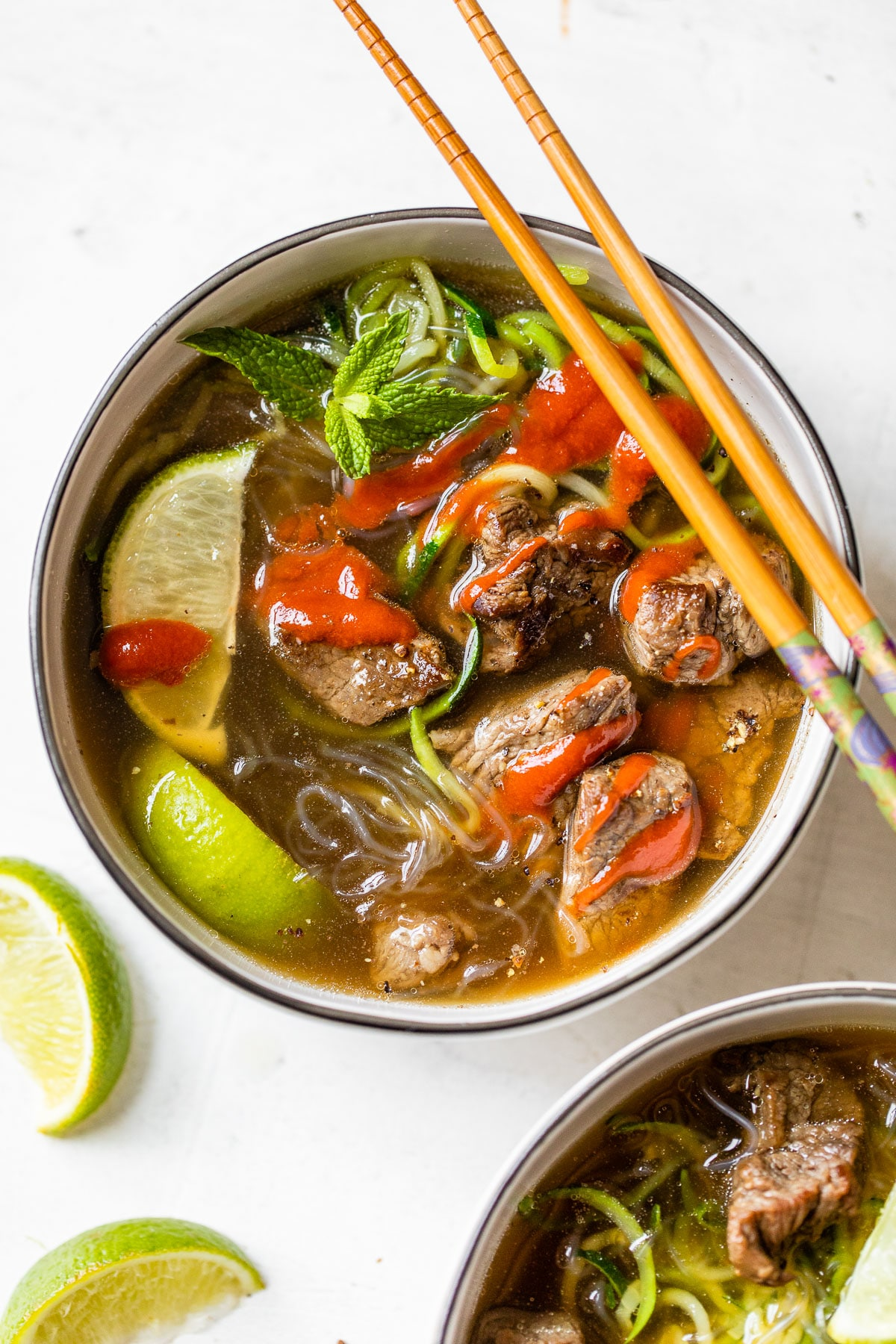 bowl of soup with noodles, beef and lime wedges