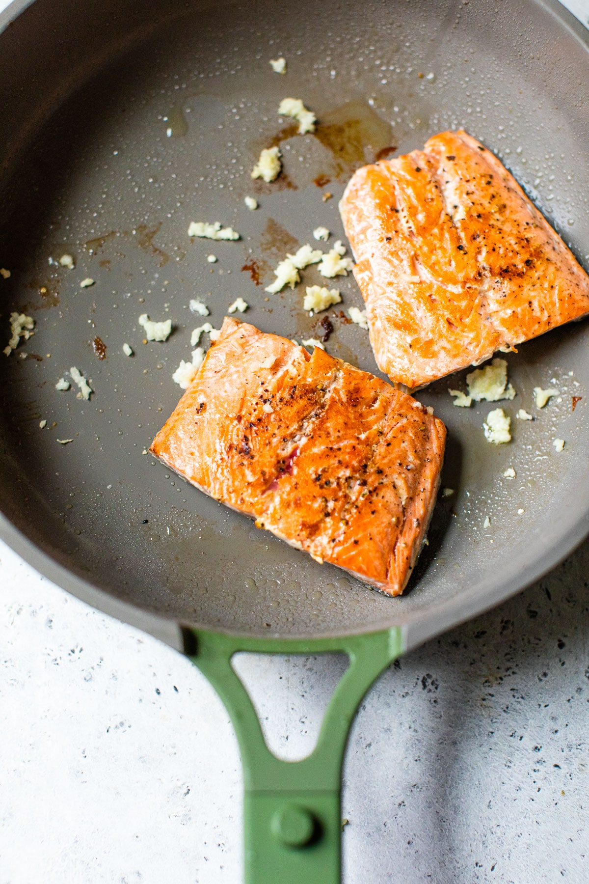 seared salmon in a skillet with garlic