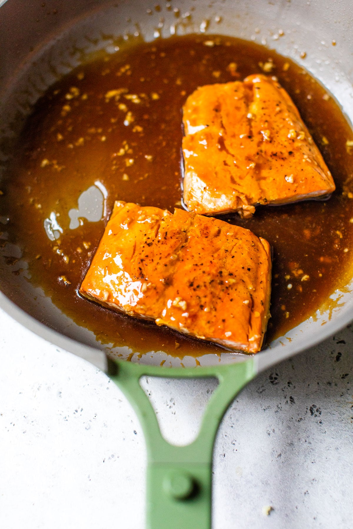 cooked salmon in a skillet with teriyaki sauce