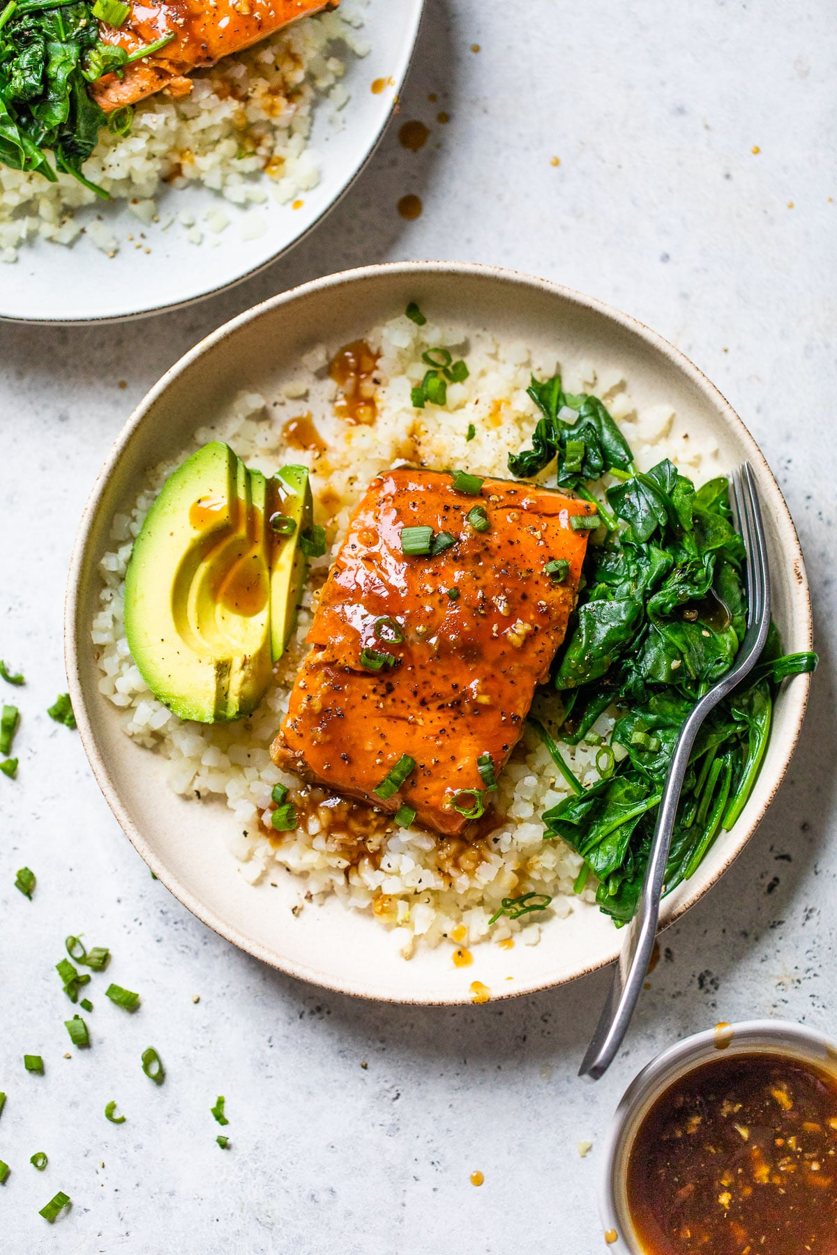 bowl filled with cauliflower rice, spinach, avocado, and cooked salmon