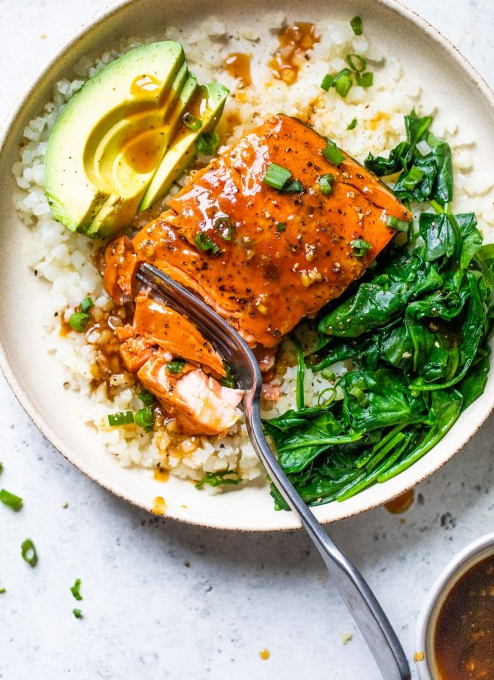 a bowl filled with cauliflower rice, salmon, cooked spinach, and avocado slices