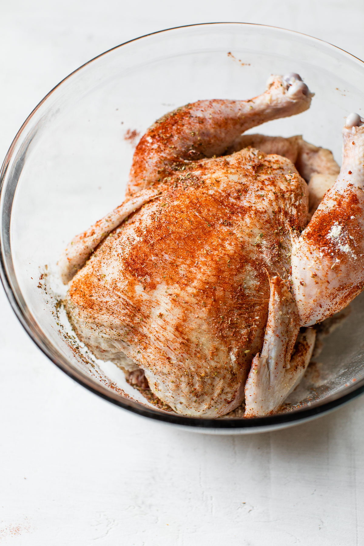 raw whole chicken in a bowl coated in dry rub