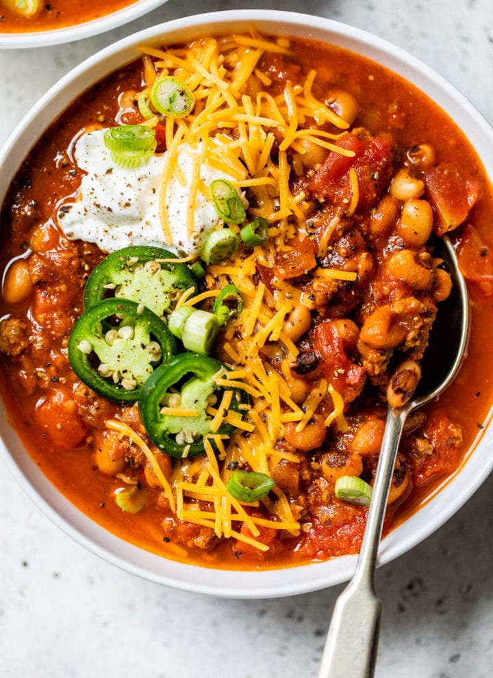 bowl of soup topped with shredded cheese and sour cream