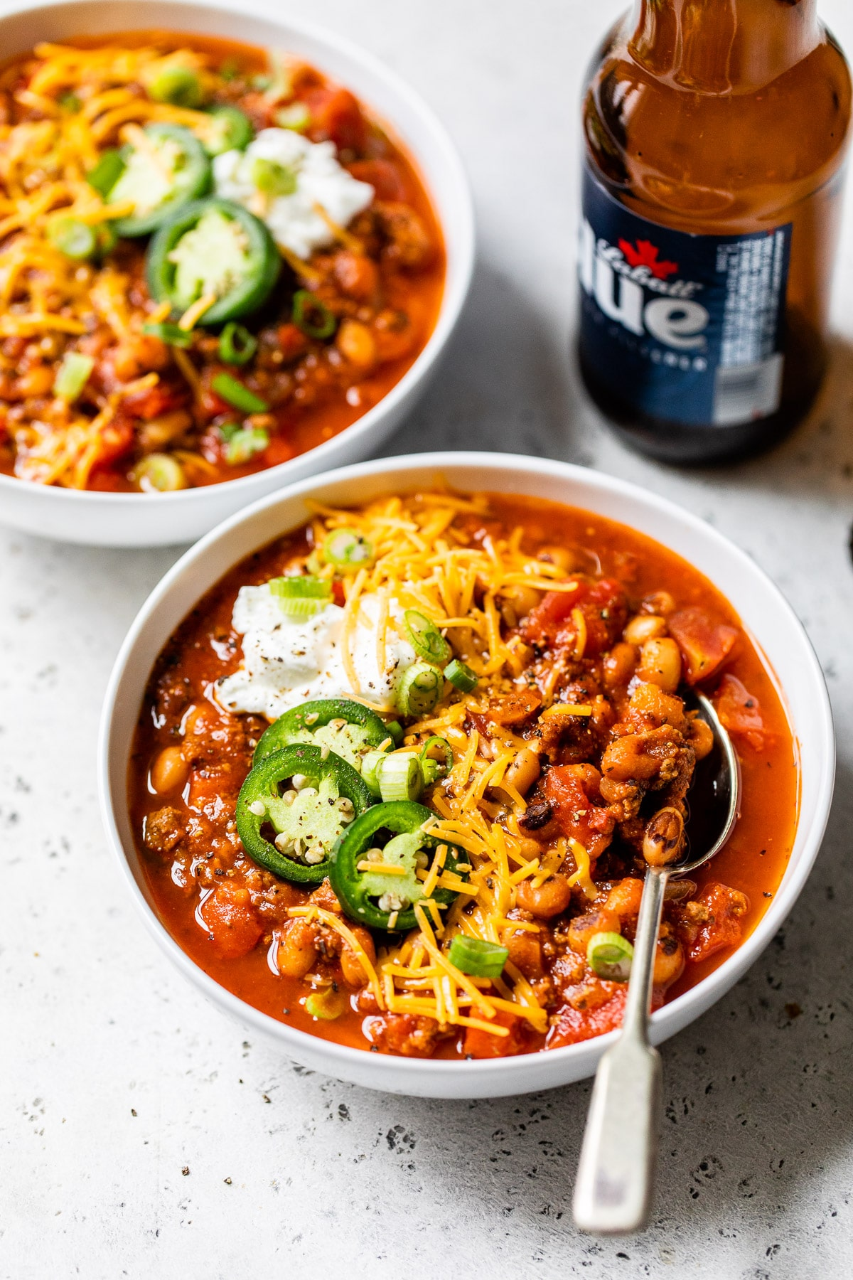 bowl of chili next to a bottle of beer