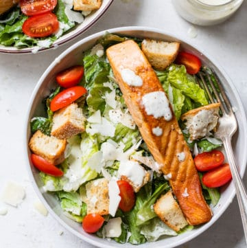 bowl of lettuce topped with grape tomatoes and cooked salmon