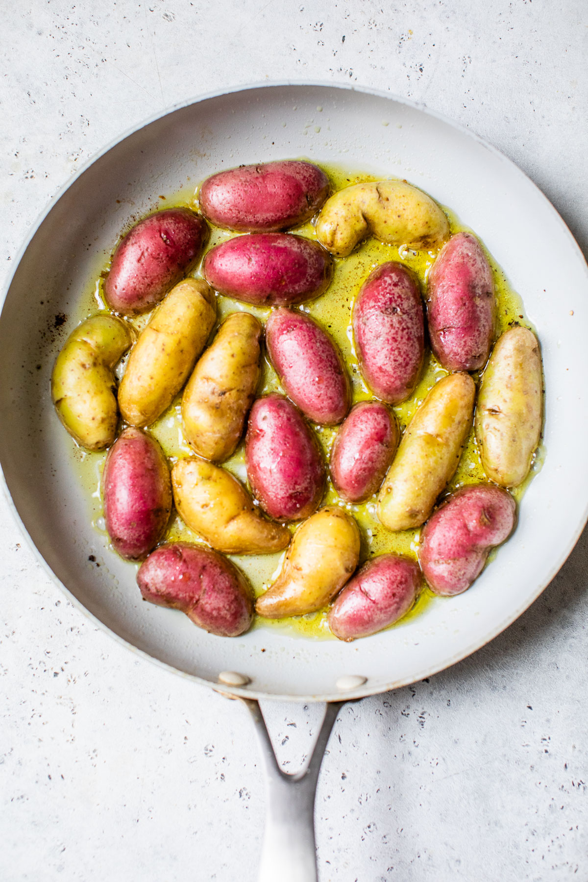 potatoes cooking in a skillet with olive oil