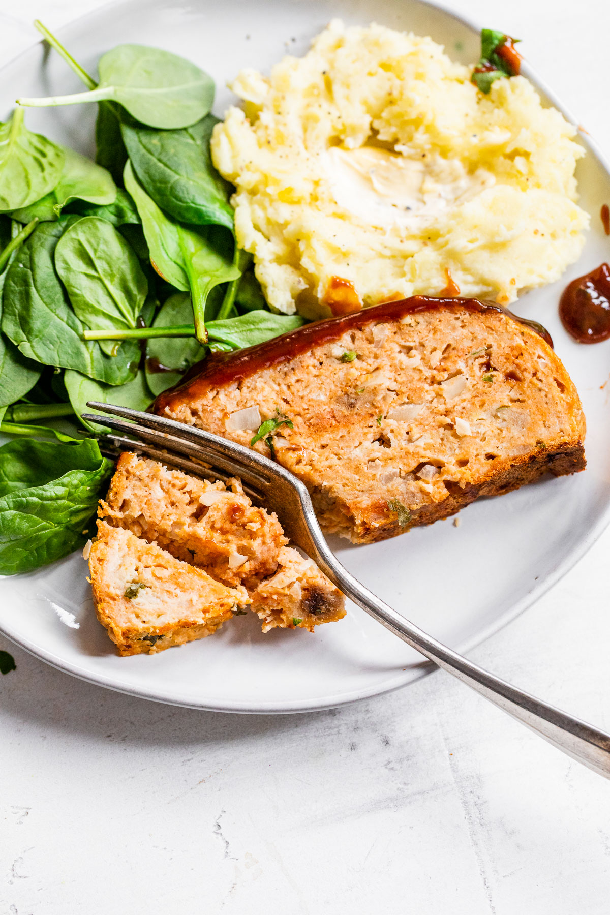 meatloaf, spinach and mashed potatoes on a plate