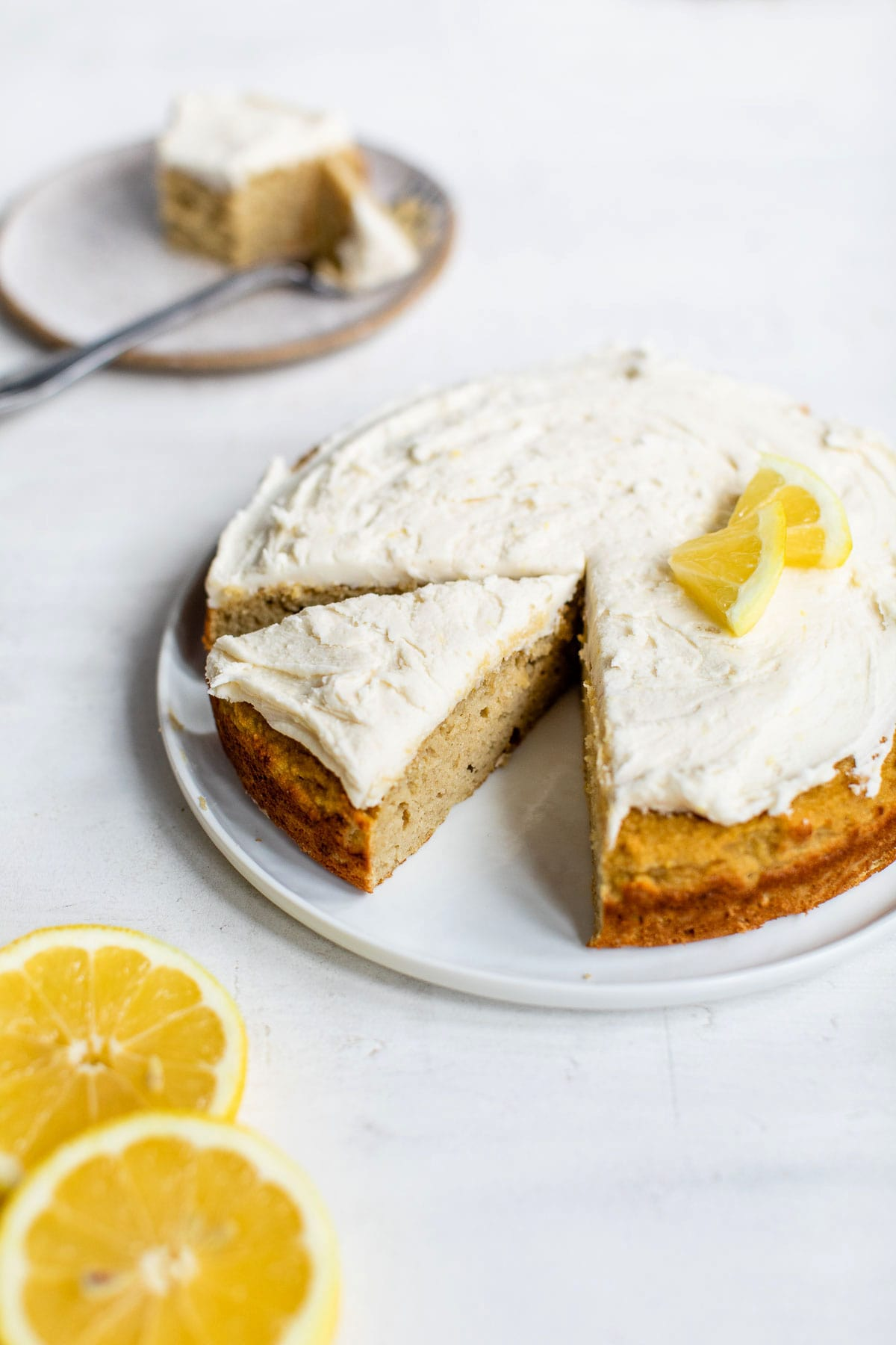 round cake on a plate topped with icing and lemon wedges