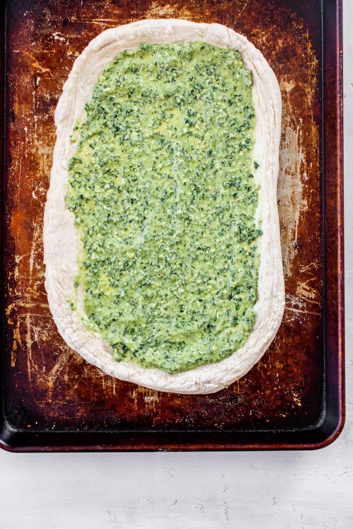 unbaked pesto pizza dough on a baking sheet