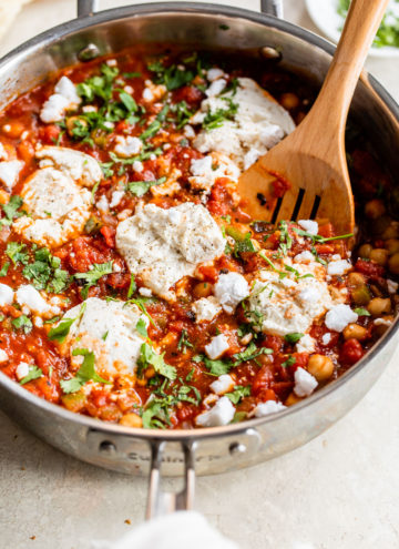 skillet filled with chickpeas, tomatoes, vegan cheese, and chopped cilantro