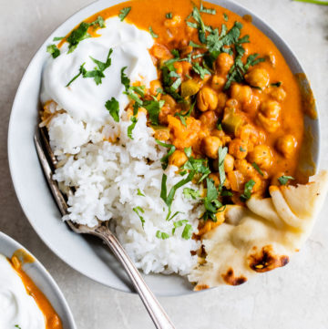 rice, naan and marinated chickpeas in a bowl with cilantro
