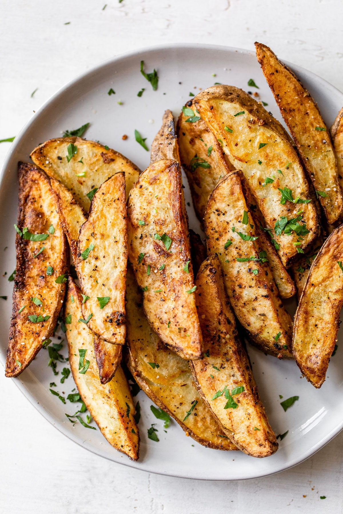 crispy seasoned potato wedges on a white plate