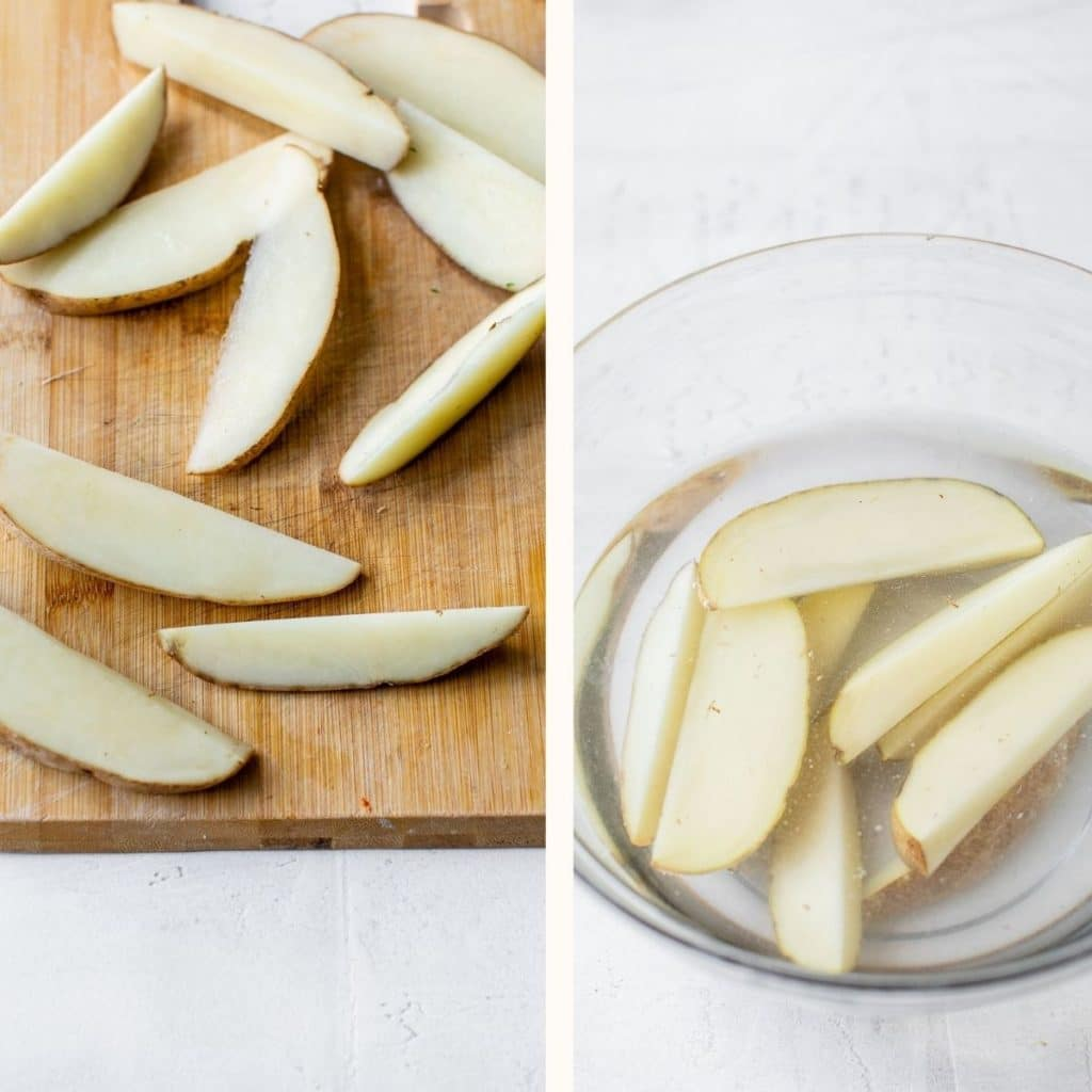 potato being sliced on a wooden cutting board