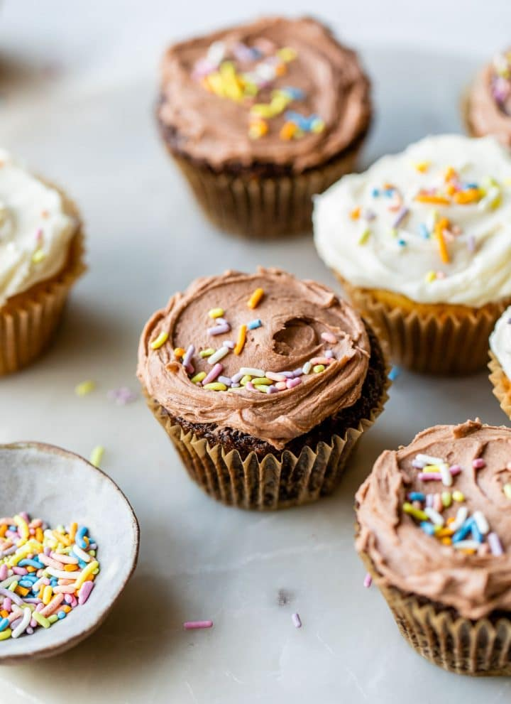 chocolate and vanilla cupcakes topped with rainbow sprinkles on a marble board
