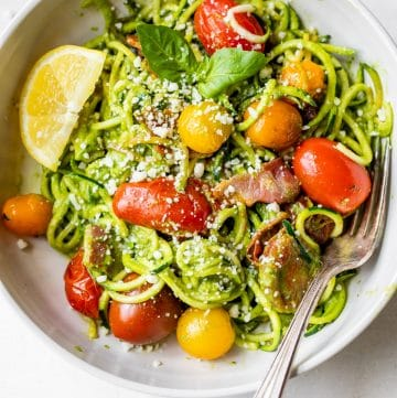 zucchini noodles in a bowl with tomatoes and bacon