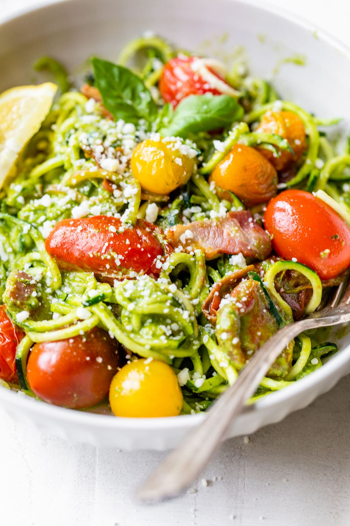 close up of pesto zucchini noodles in a bowl