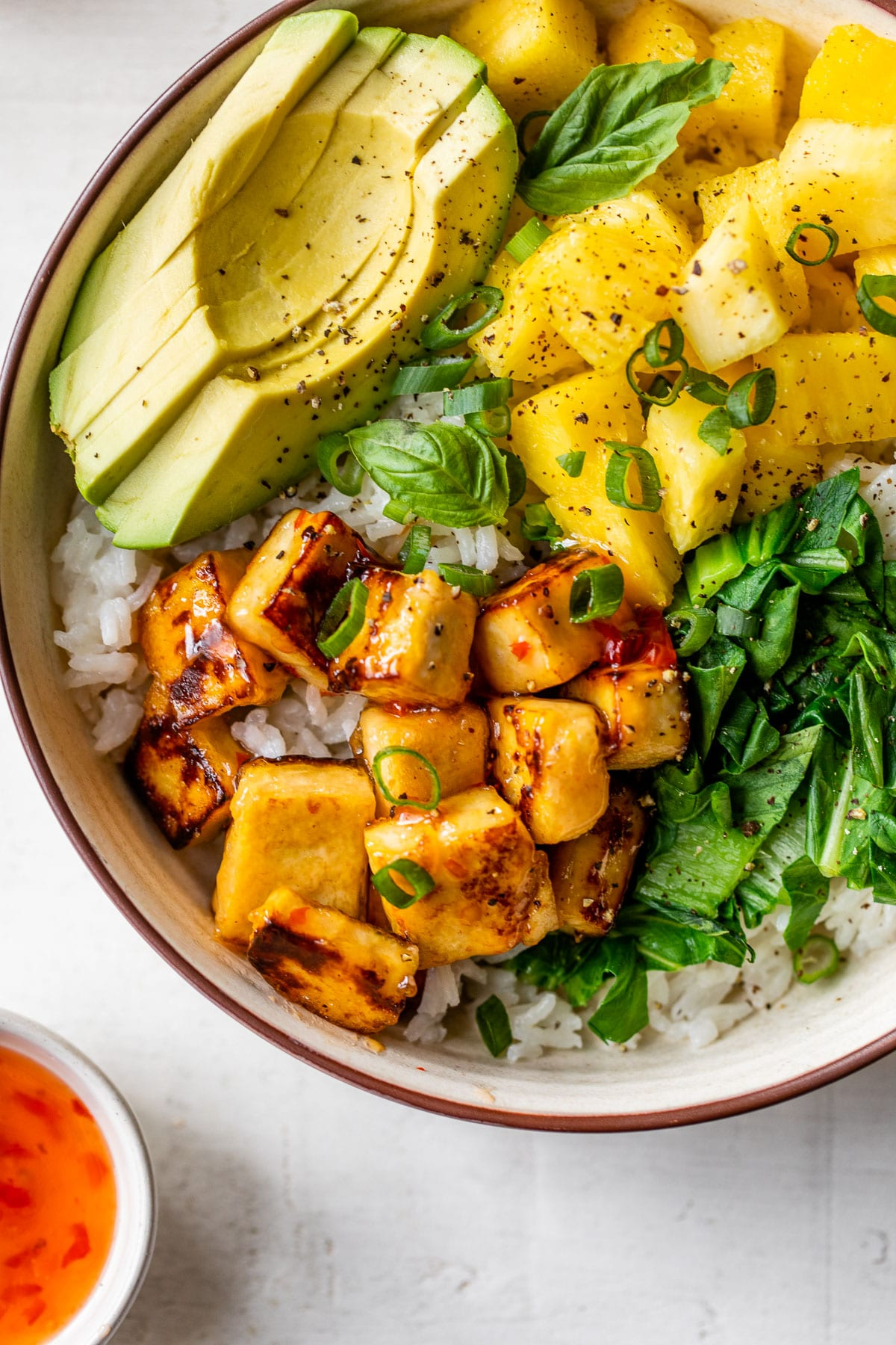 close up photo of crispy tofu in a bowl with rice and sliced avocado