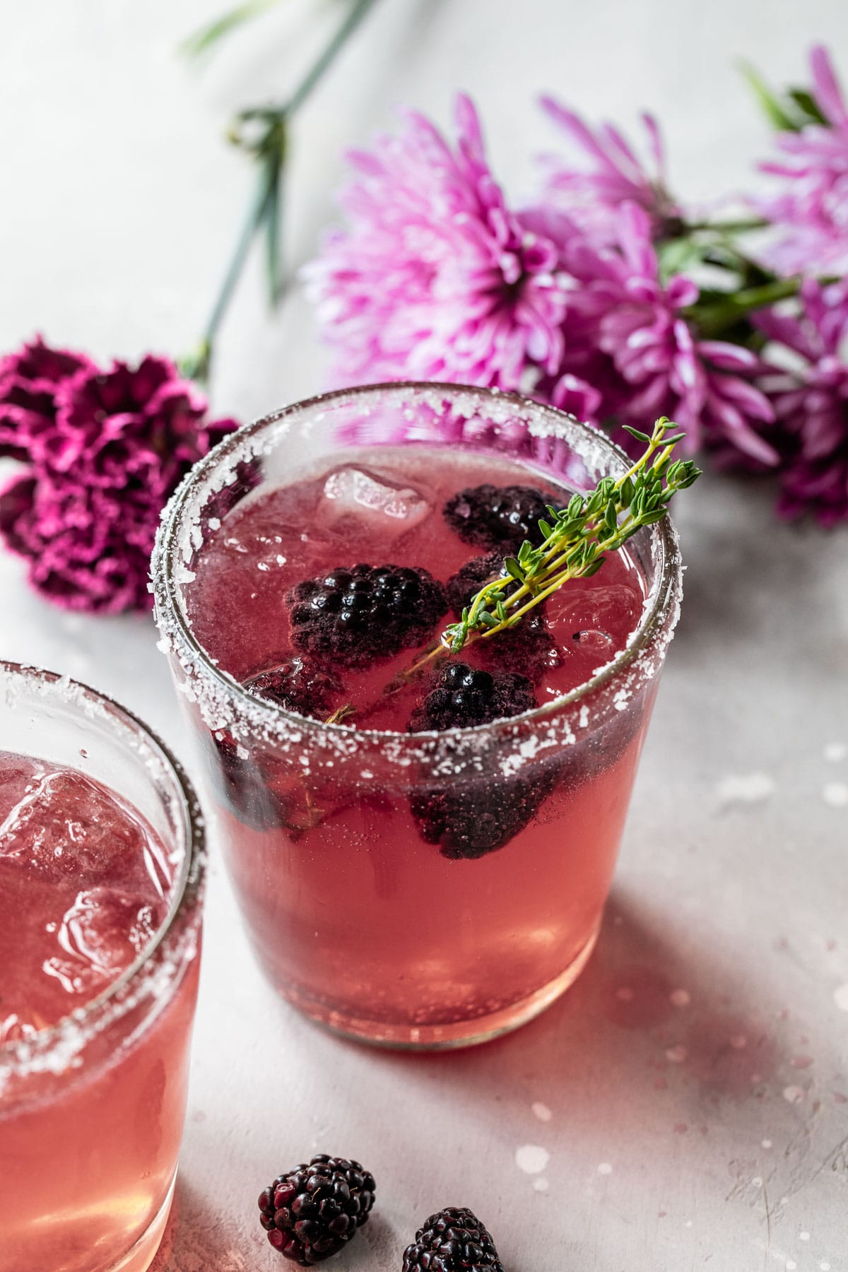 purple cocktail with blackberries and purple flowers in the background