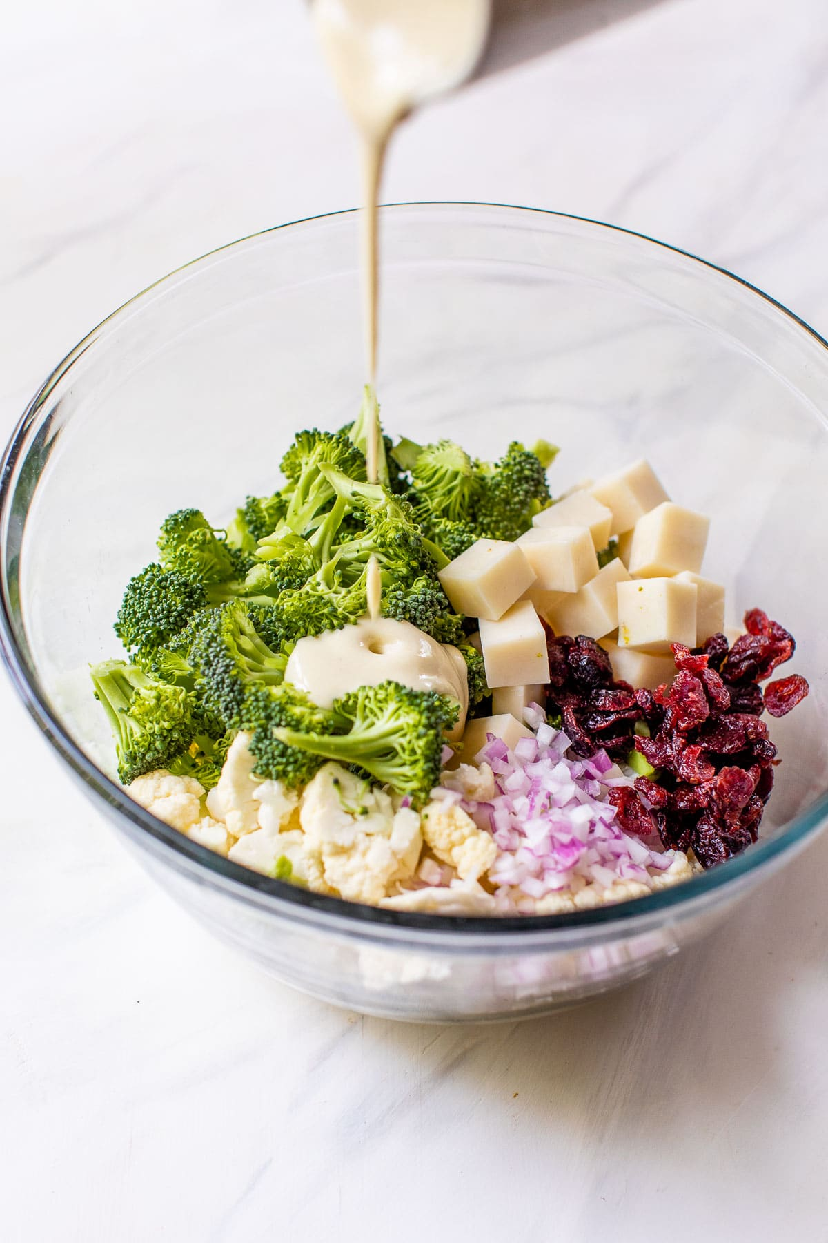 someone pouring a dressing over top of chopped broccoli and cauliflower in a bowl