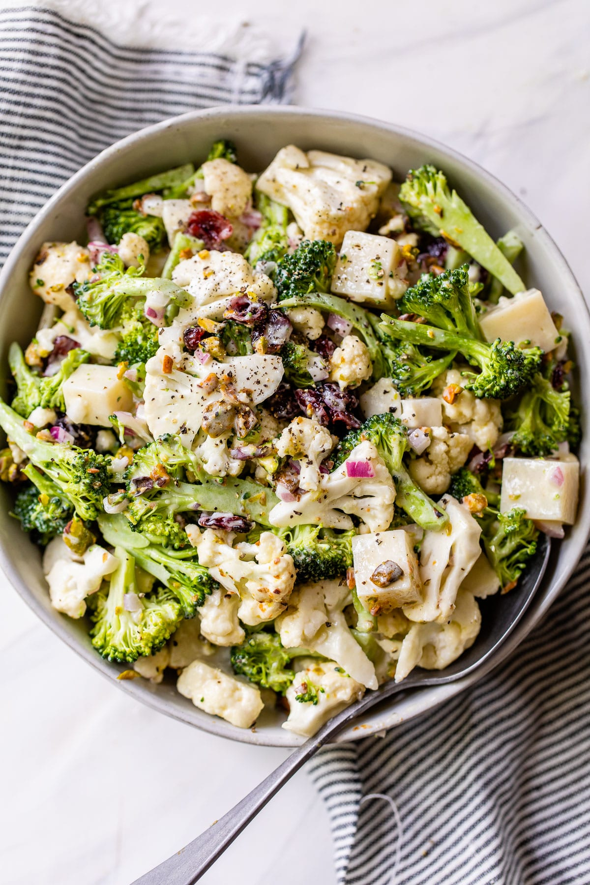 a large bowl filled with broccoli, cauliflower, cheese, and dried cranberries on top of a striped linen