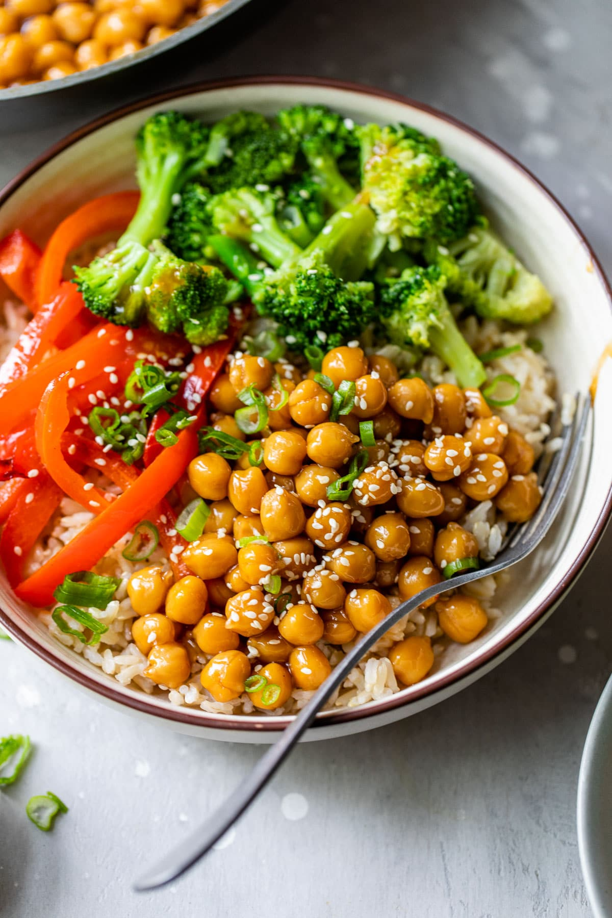 bowl filled with rice, broccoli, red bell pepper, and marinated chickpeas