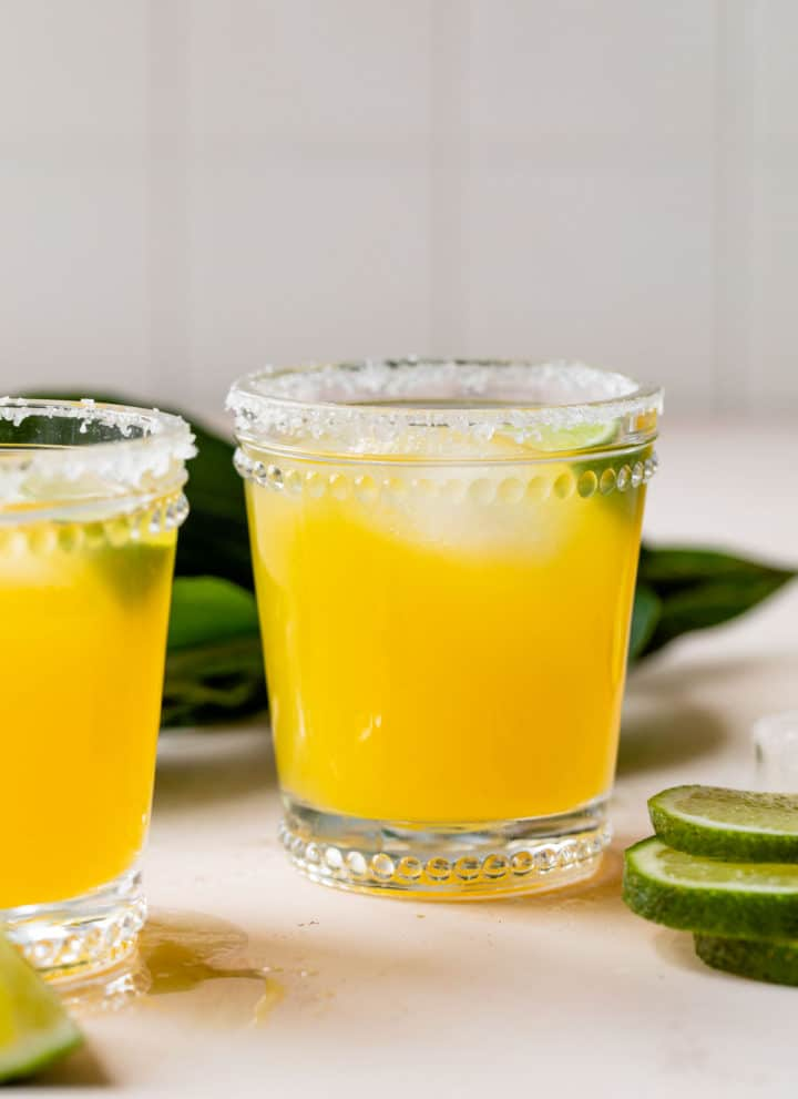 mango margarita in a glass with lime wedges