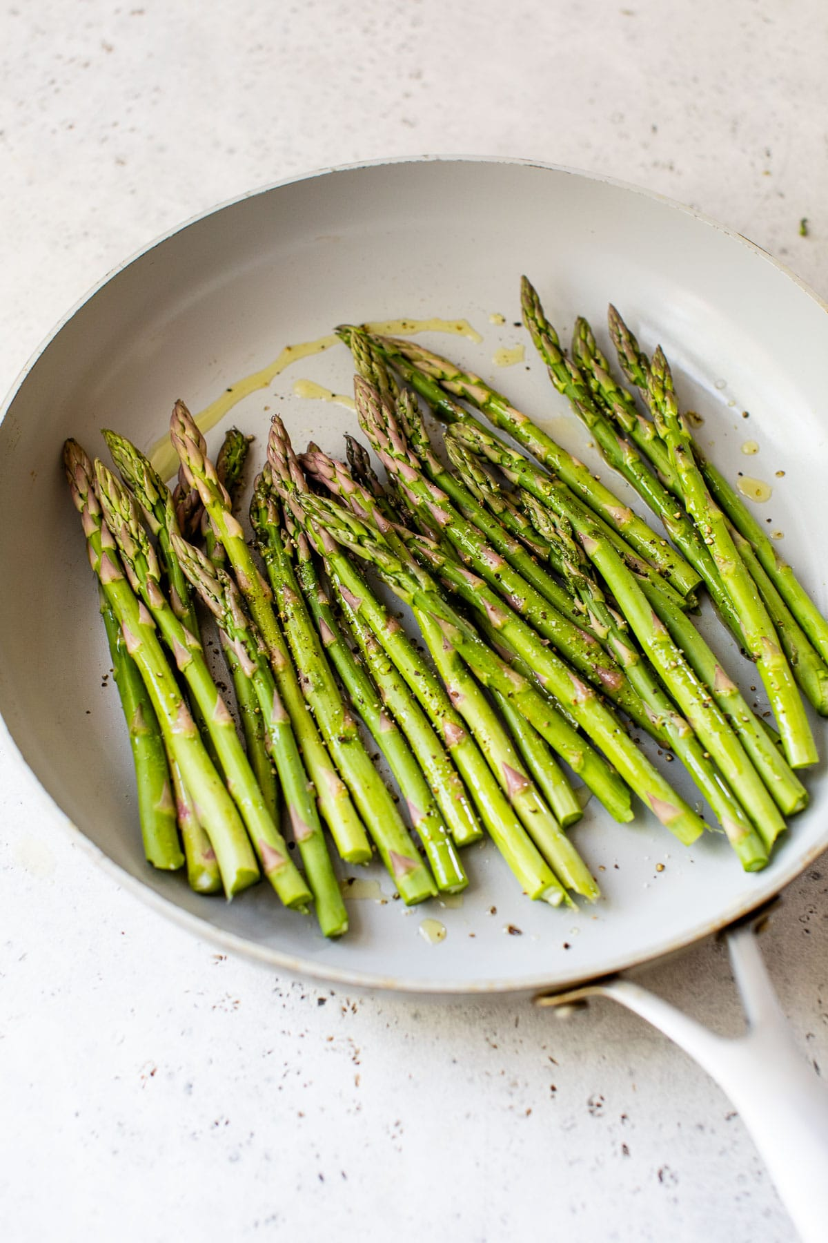 raw asparagus in a skillet drizzled with olive oil