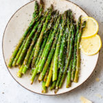 cooked asparagus on a plate with lemon wedges