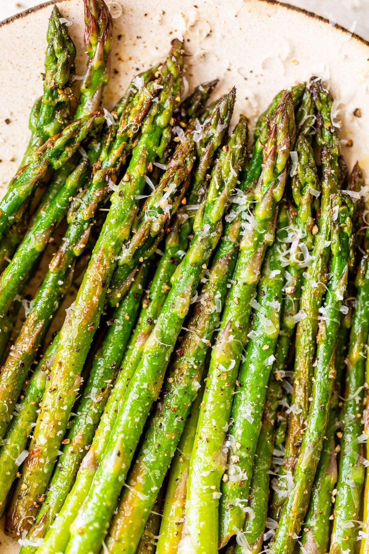 close up of asparagus sprinkled with shredded parmesan cheese