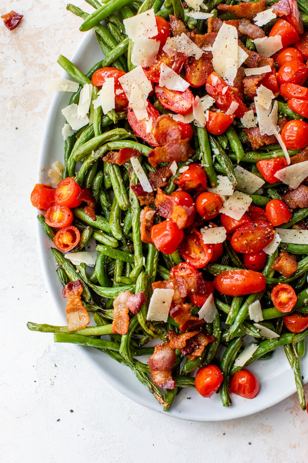 green beans, tomatoes, bacon, and shaved parmesan on an oval platter