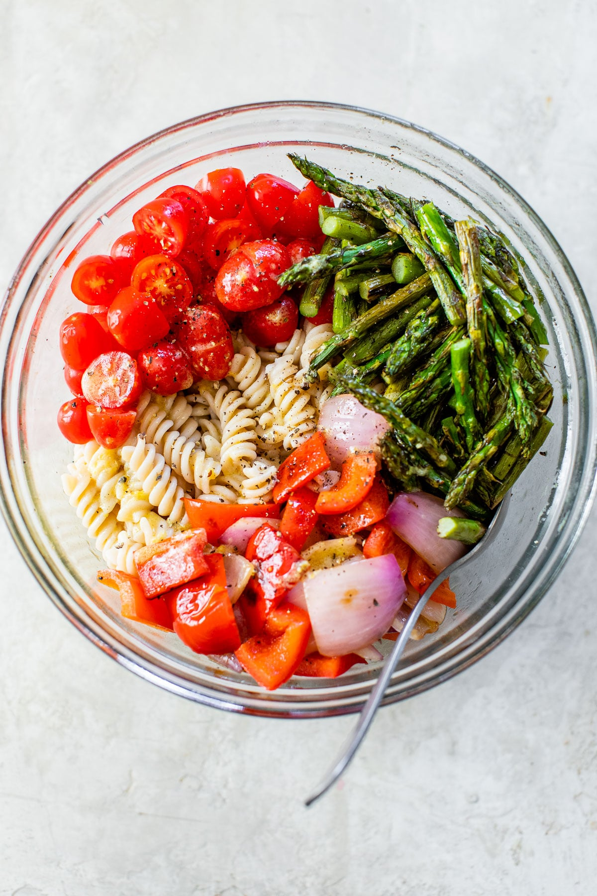 cooked rotini pasta in a bowl with asparagus, tomatoes, onion, and bell pepper