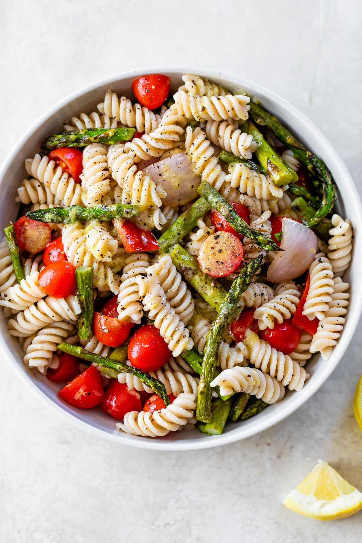 large white bowl with grilled asparagus, rotini pasta and other vegetables