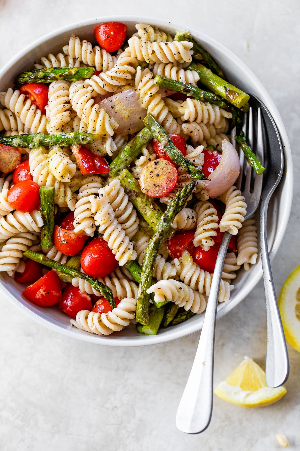 rotini pasta in a white bowl with chopped asparagus, tomatoes and red onion