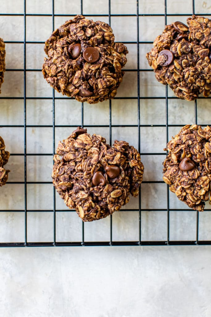 chocolate oatmeal cookies cooling on a black cooling rack