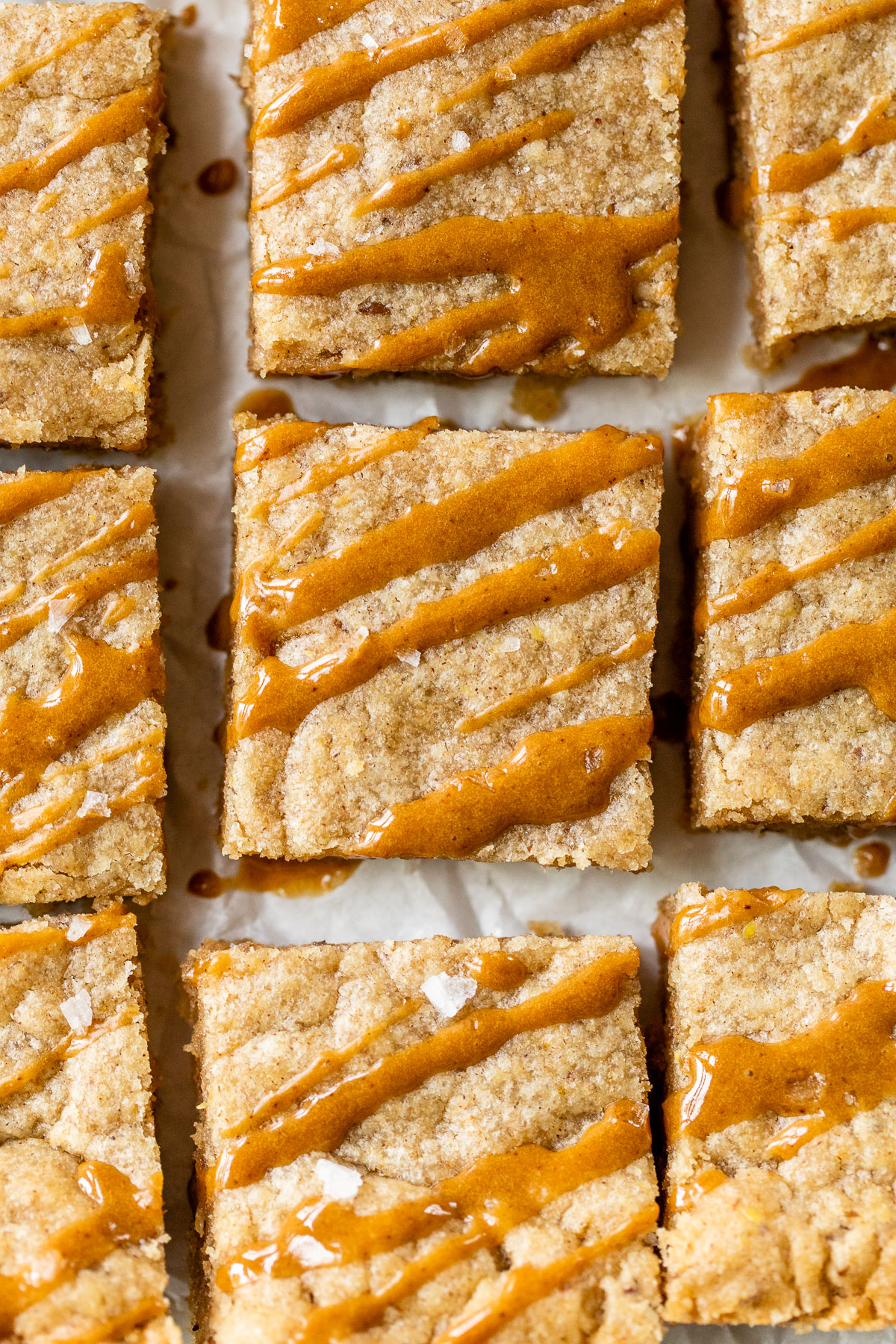 bars on parchment paper with a caramel-colored drizzle of icing on top