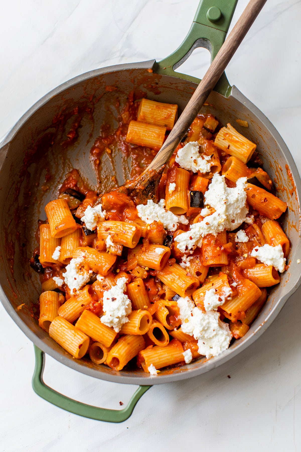 skillet filled with rigatoni pasta and dollops of ricotta cheese